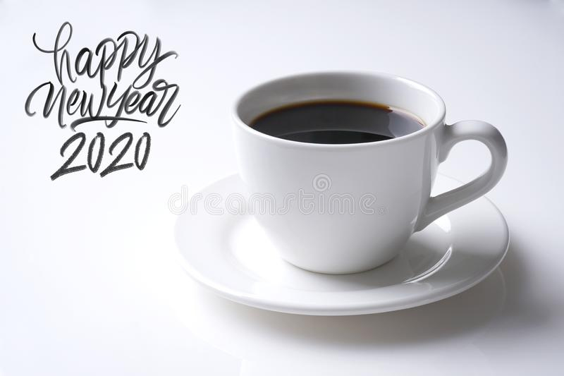 Happy new year 2020. Cup of black coffee and happy new year 2020 great hand latter on white stock photography