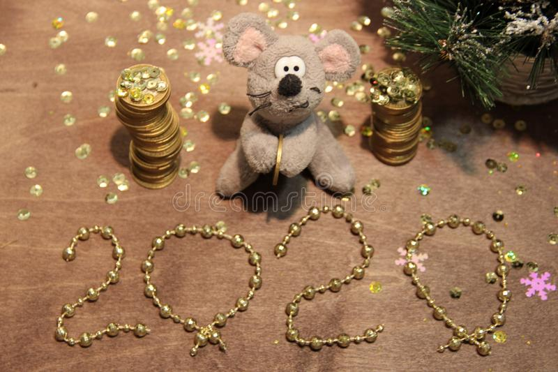 Happy New Year 2020. Grey rat and money, wishes for wealth and profit. Golden background. Merry Christmas. royalty free stock images